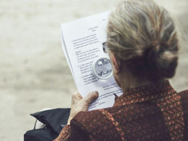 The picture shows a lady with a magnifying glass.